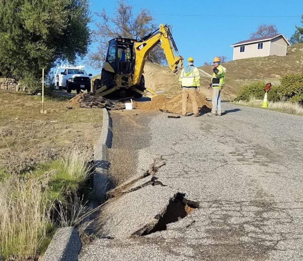 Backhoe digging out old pipe.